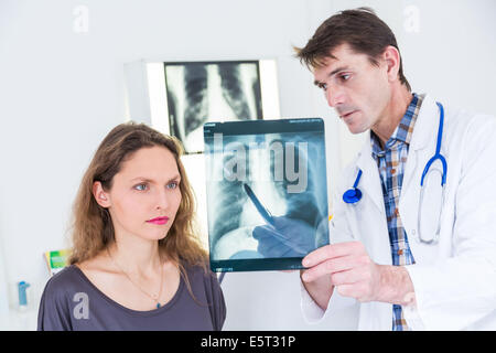 Doctor examining and commenting patient's lungs X-ray. - Stock Photo