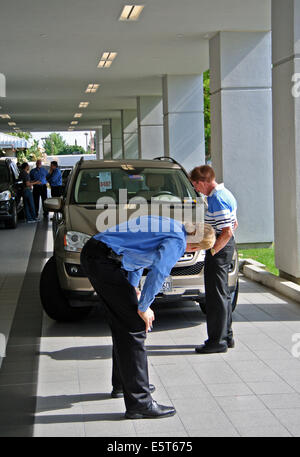 Mercedes Benz service manager checks out customers car at dealer check in - Stock Photo