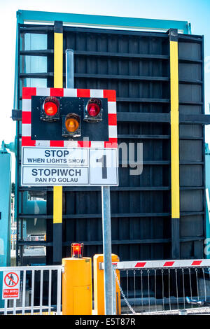 Stop barrier warning lights and raised bascule bridge across the locks in Cardiff Bay barrage - Stock Photo