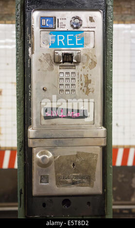 An abandoned coin operated public pay telephone on a subway station platform in New York - Stock Photo