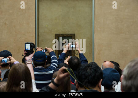 Tourists taking pictures of Mona Lisa painting in the Louvre Museum in Paris, France - Stock Photo