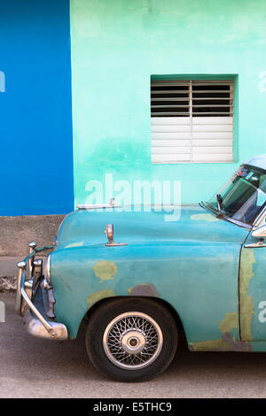 Vintage American car in front of the green and blue walls of a colonial building, Trinidad, Sancti Spiritus, Cuba, - Stock Photo