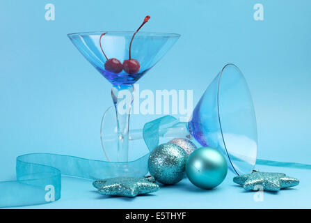 Festive spirit blue martini cocktail glasses with red maraschino cherries and Christmas baubles on an aqua blue - Stock Photo