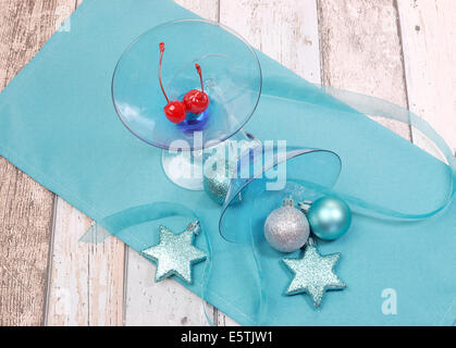 Festive spirit blue martini cocktail glasses with red maraschino cherries and Christmas baubles on a shabby chic - Stock Photo
