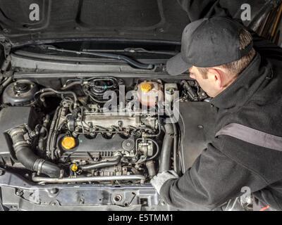 Auto mechanic inspecting car engine compartment - Stock Photo