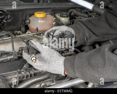 Auto mechanic replacing broken Diesel glow plug wire in car diesel engine compartment - Stock Photo
