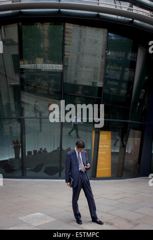 Businessman checks messages beneath modern office entrance architecture on Walbrook, City of London. - Stock Photo