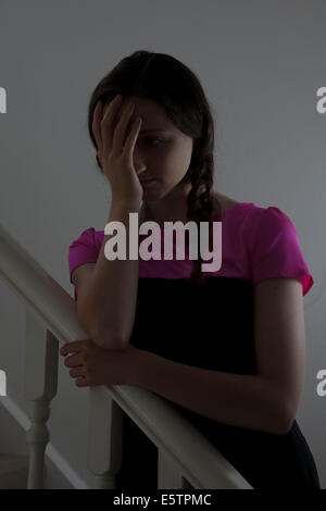 Young female wearing a pink top and hair in plats standing on the stairs indoors, hand on face. - Stock Photo
