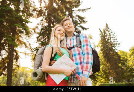 smiling couple with map and backpack in nature - Stock Photo