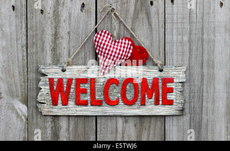 Red welcome sign with red checkered hearts on wooden background - Stock Photo