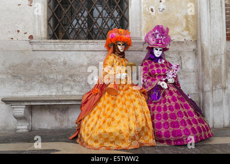 Costumed people on the Piazza San Marco during Venice Carnival - Stock Photo