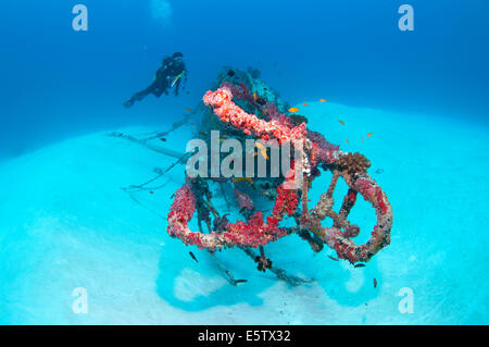 Diver and a small wreck on a sandy sea floor south of Bolifushi island, south Male' Atoll in Maldives - Stock Photo