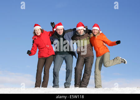 Friends with Santa hats have fun on flank of hill - Stock Photo