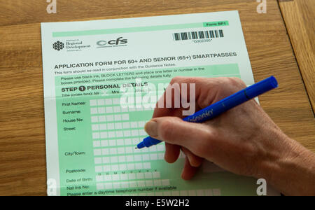 Woman completing an application form for 60+ and Senior 65+ Smartpasses, Northern Ireland - Stock Photo