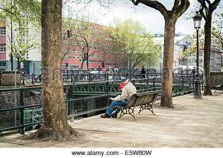 Man reading on a park bench along the Canal St. Martin in spring, Paris, Îsle-de-France, France - Stock Photo