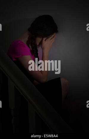 Moody shot of a young female sitting alone in the dark, with her hand covering her face. Depression and moods. - Stock Photo