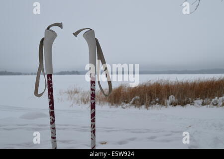 Ski poles sitting in the snow. - Stock Photo