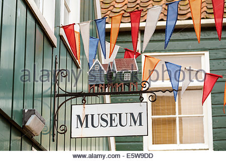 Museum sign and flags of Dutch national colors on building exterior, Marken, North Holland, Netherlands - Stock Photo