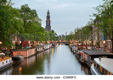 Prinsengracht canal at dusk with Westerkerk in distance, Amsterdam, North Holland, Netherlands - Stock Photo