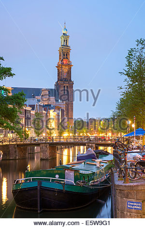 Prinsengracht canal and boat at dusk with tower of Westerkerk in distance, Amsterdam, North Holland, Netherlands - Stock Photo