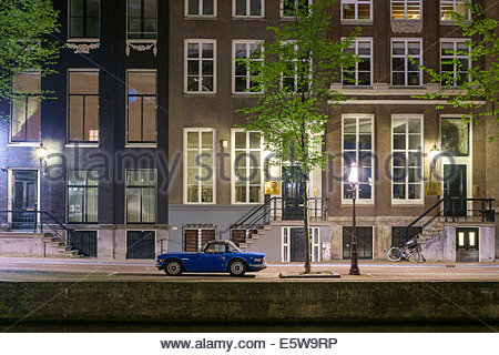 Blue car parked in front of canal houses on the Herengracht at night, Amsterdam, North Holland, Netherlands - Stock Photo