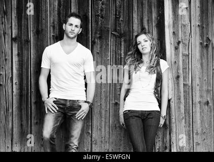 Young man and a young woman leaning against wooden wall - Stock Photo