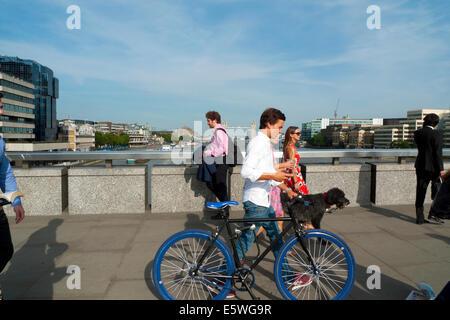 Man crossing London Bridge in summer sunshine  walking pushing a blue bicycle London UK   KATHY DEWITT - Stock Photo