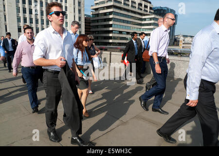 Man with sunglasses walking in crowd across London Bridge at rush hour after work in summer on a hot day London - Stock Photo