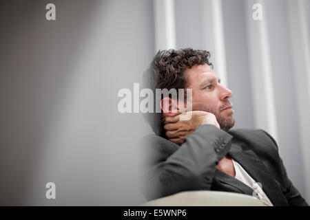 Businessman leaning on elbow - Stock Photo