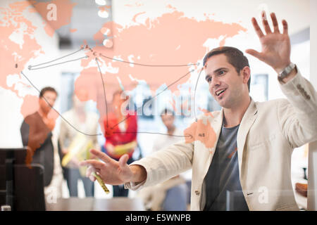 Man writing on glass screen, colleagues watching - Stock Photo
