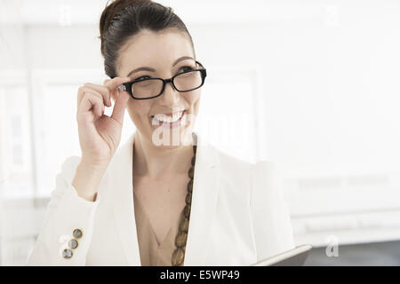 Young businesswoman looking over spectacles - Stock Photo