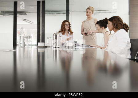 Four businesswomen meeting in conference room - Stock Photo