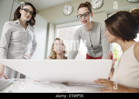Four businesswomen looking at blueprint in office - Stock Photo