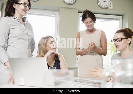 Four businesswomen at presentation meeting in conference room - Stock Photo