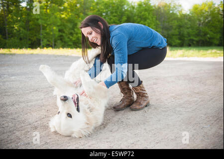 Young woman petting golden retriever on roadside - Stock Photo