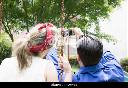 Rear view of young vintage couple taking selfie with camera in garden - Stock Photo