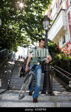 Mid adult male carrying bicycle down stairway in Paris, France - Stock Photo