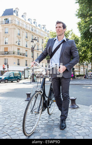 Mid adult businessman pushing bicycle over cobbles, Paris, France - Stock Photo