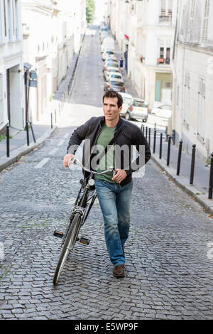 Mid adult man pushing bicycle up cobbled city street - Stock Photo