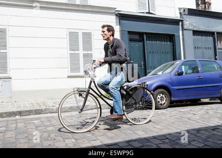Mid adult man speeding down cobbled city street on bicycle - Stock Photo