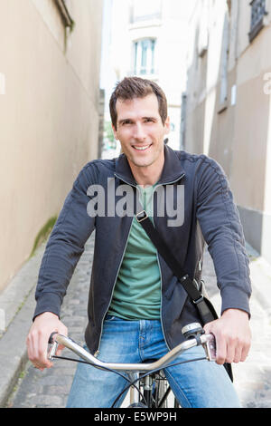Portrait of mid adult man on bicycle in city street - Stock Photo