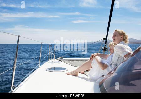 Mid adult mother son sailing on catamaran near Fuerteventura, Spain - Stock Photo