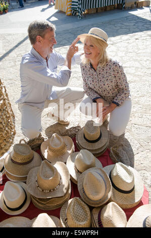 Couple shopping for hat at market, Mallorca, Spain - Stock Photo