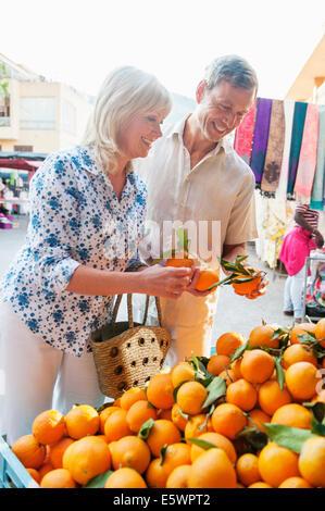 Couple choosing oranges at market, Mallorca, Spain - Stock Photo