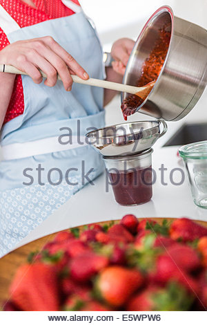 Woman pouring strawberry jam into jar - Stock Photo