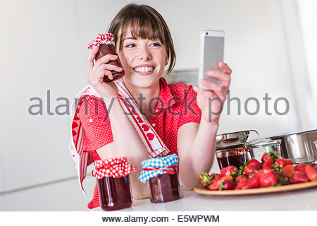 Woman taking selfie with strawberry jam jar - Stock Photo