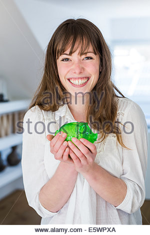 Woman holding green piggy bank - Stock Photo