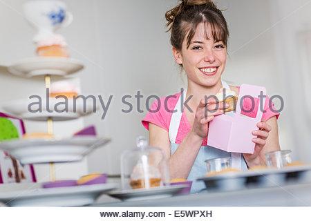 Woman packing homemade cupcakes - Stock Photo
