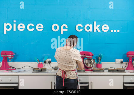 Rear view of young woman using blender in bakery - Stock Photo