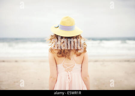 Rear view of teenage girl standing in front of sea, Hampton, New Hampshire, USA - Stock Photo